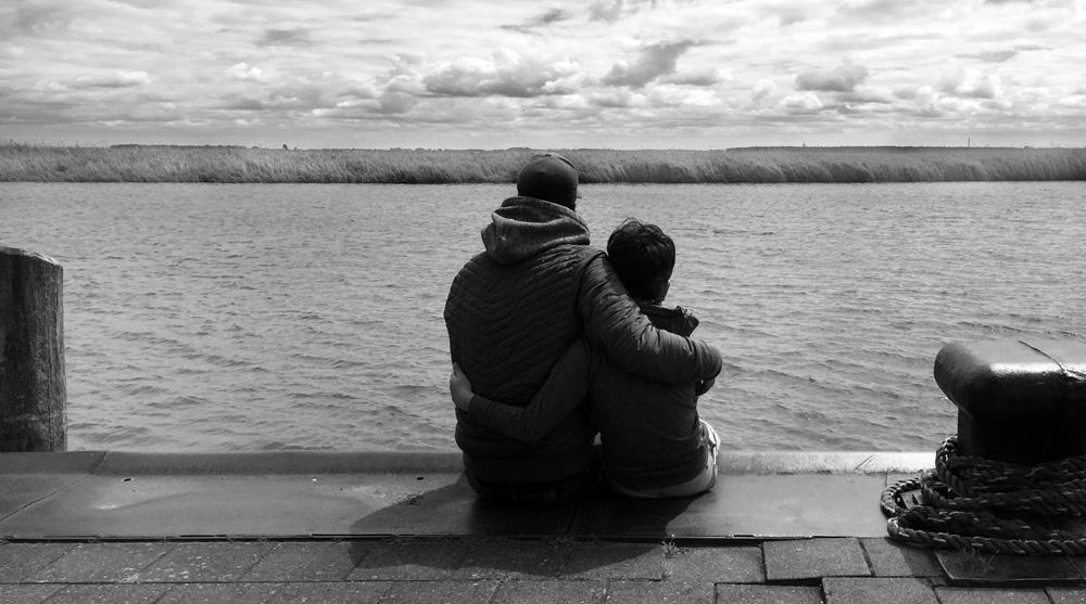 Vater und Sohn schauen auf einen Fluss