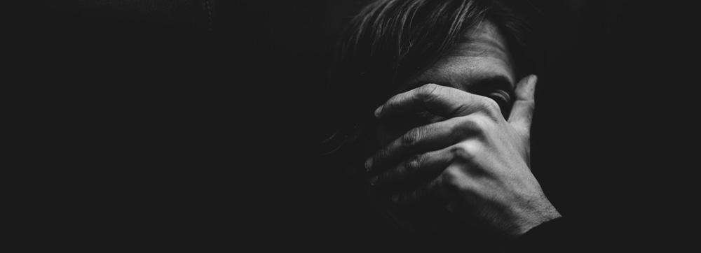ein Mann im Dunkeln hält die Hand vor sein Gesicht