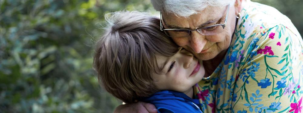 eine Großmutter umarmt ihren Enkel
