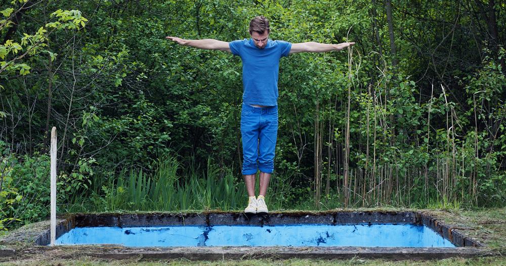 ein Mann simuliert im Wald den Sprung in ein Badebecken