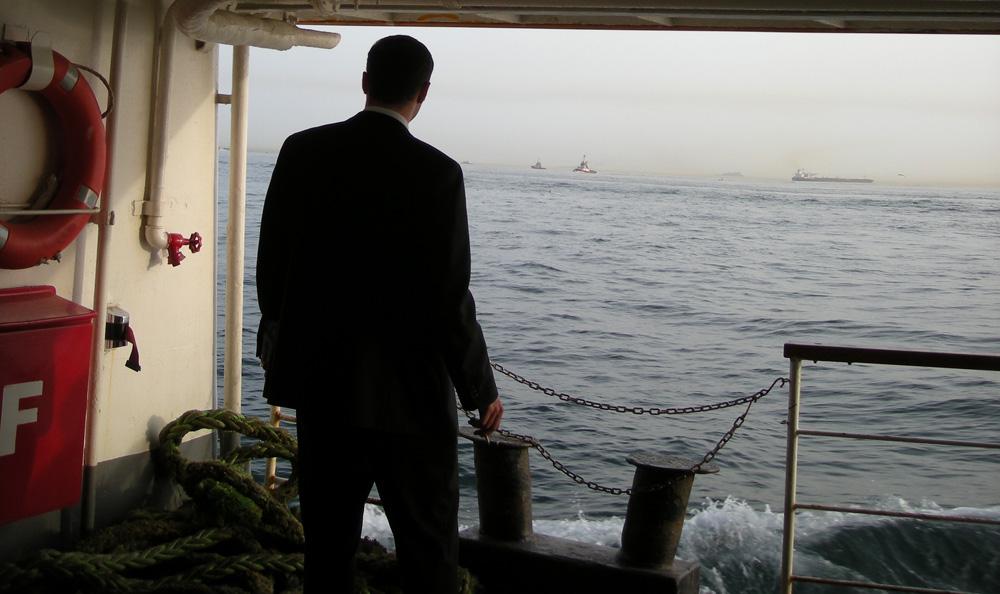 ein Mann steht auf einer Fähre und schaut auf den Horizont