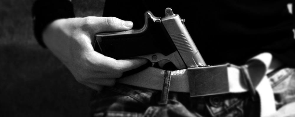 eine Pistole im Hosenbund eines Mannes