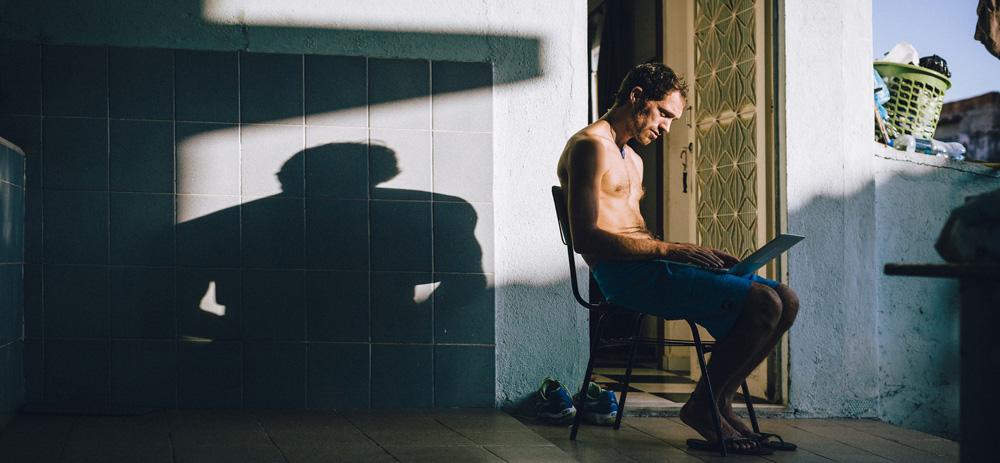 Ein Mann sitzt mit einem Laptop auf einem Balkon