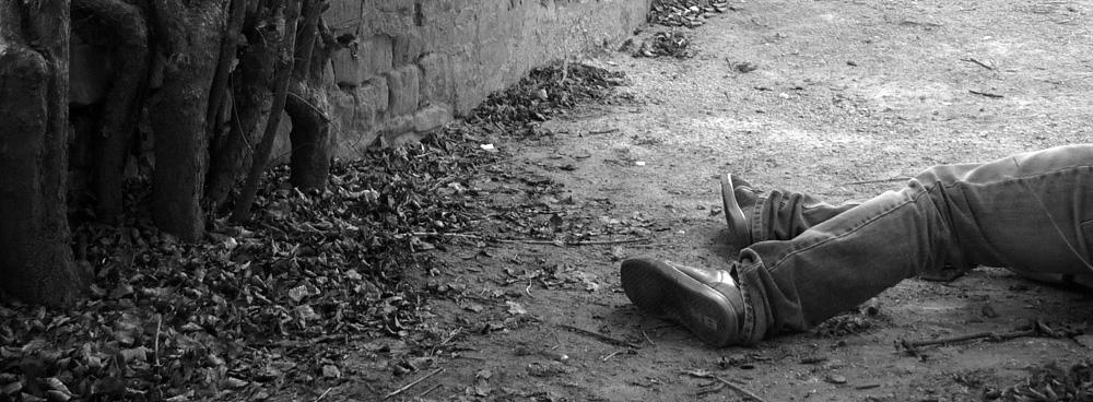 Beine eines Mannes, die auf dem Bpden liegen