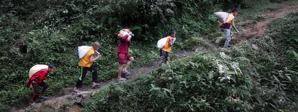 Fünf Jungen tragen Lasten einen Berg hoch