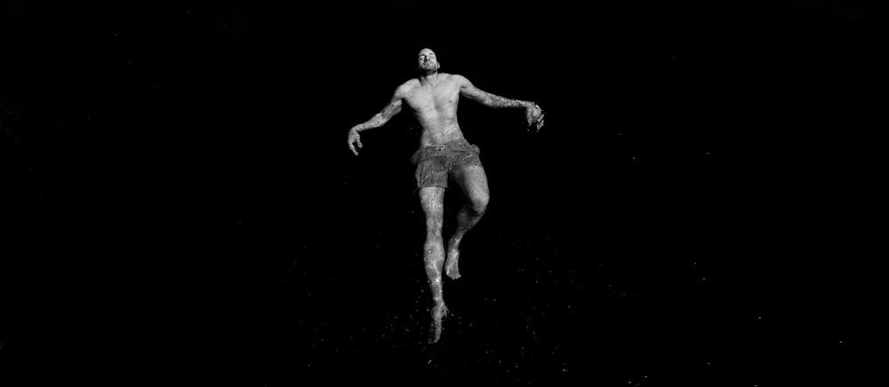 ein Mann lässt sich rücklings im Wasser reiben