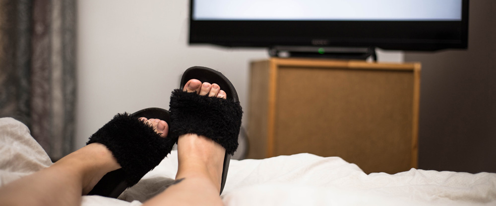 Zwei Füße im Bett vor einem Fernseher