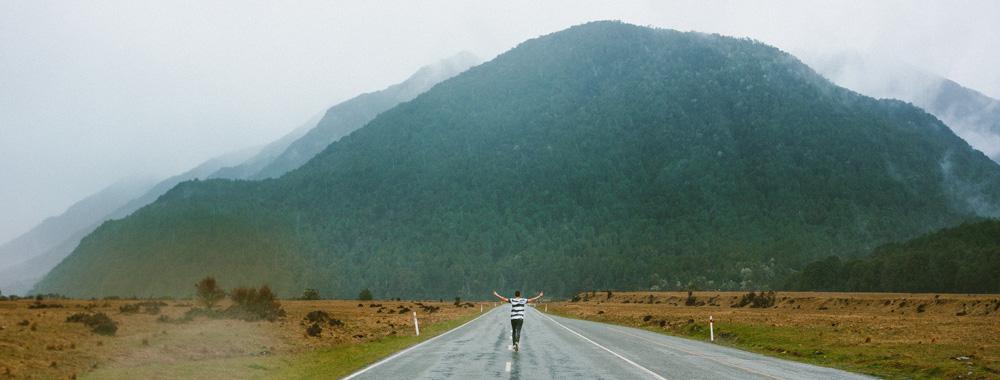 ein Mann läuft auf einer Straße einem Gebirge entgegen