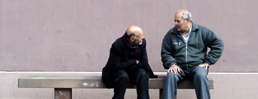 Zwei Männer auf einer Bank unterhalten sich