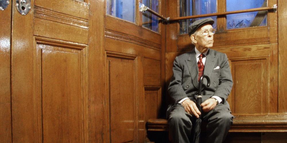 Alter Mann mit Schirm sitzt in einem Fahrstuhl