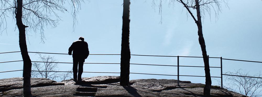 Ein Mann schaut am Geländer eines Gebirsgweges in die Tiefe