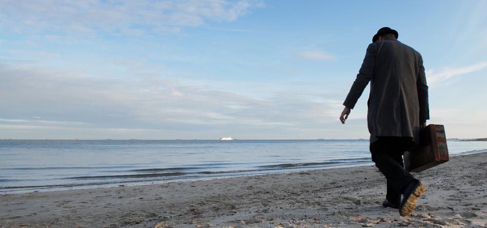 Ein Mann mit einem Koffer geht Richtung Meer