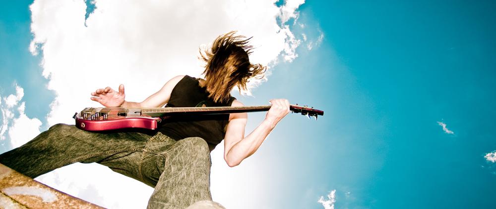 Junger Musiker auf einer Mauer