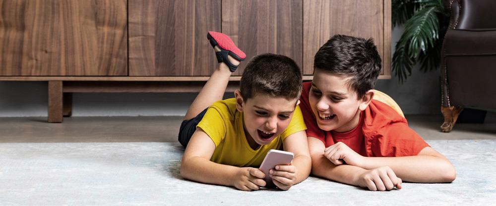 Zwei Jungs spielen mit Smartphone im Wohnzimmer