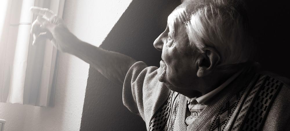 Alter Mann zeigt mit dem Finger zum Fenster