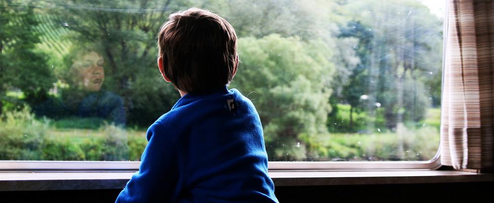 Junge schaut aus einem Fenster