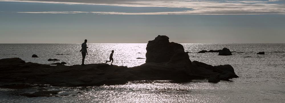 Vater und Sohn am Meer im Gegenlicht