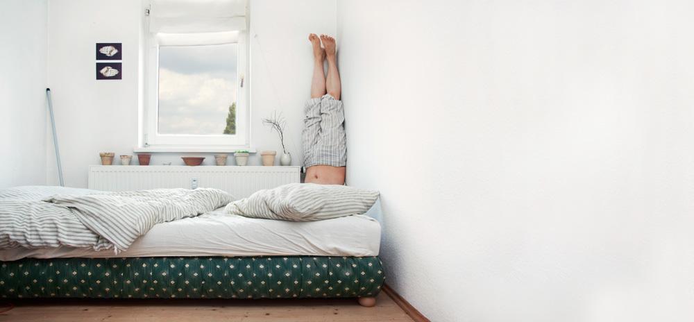 Mann macht Kopfstand in der Ecke seines Schlafzimmers