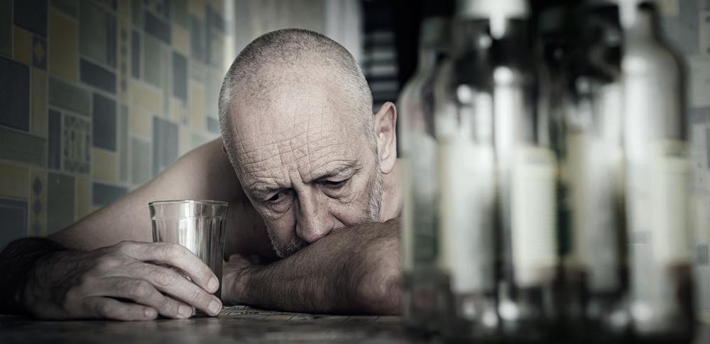 Ein nachdenklicher Mann am Tisch mit einem Glas und Flaschen