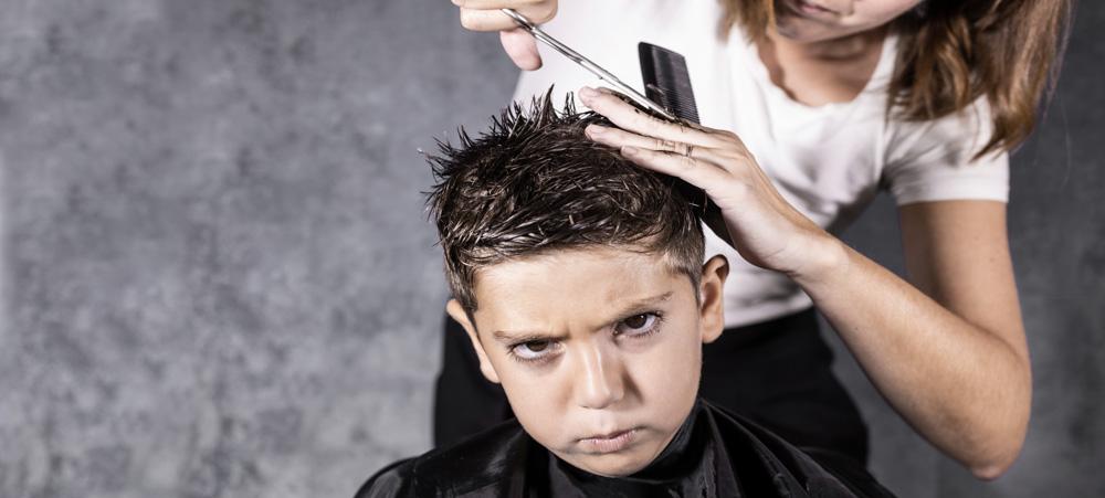 Junge bekommt die Haare von seiner Mutter geschnitten
