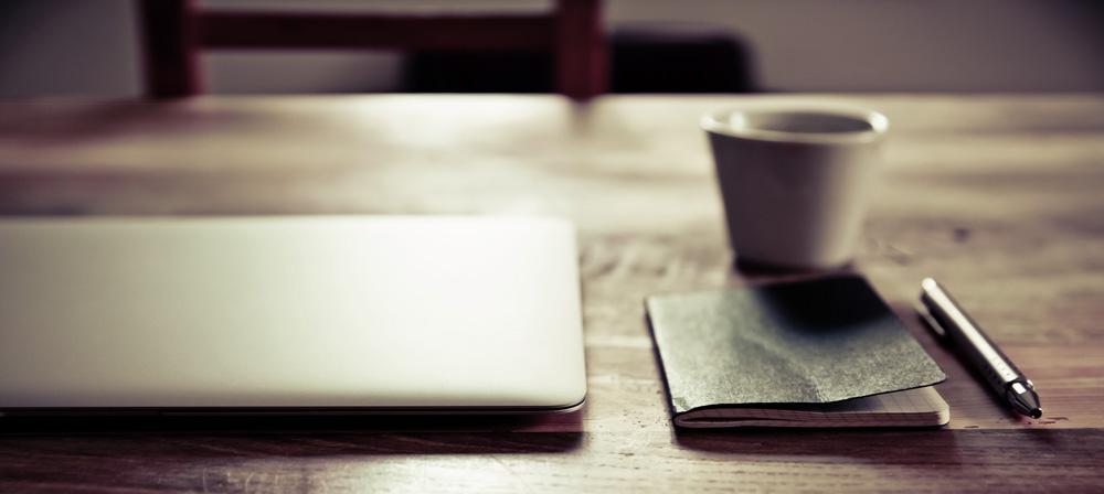 ein Tisch mit Laptop, Notizbuch, Stift und Tasse