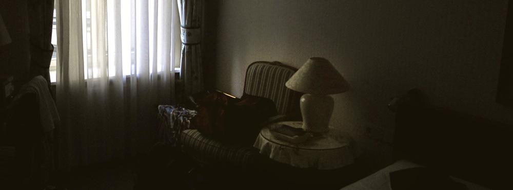 Dunkles Zimmer mit Licht vom Fenster hinter einem Vorhang