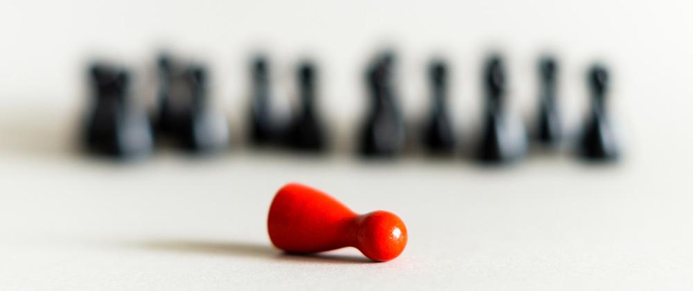Schwarze Spielfiguren stehen und eine rote Spielfigur liegt