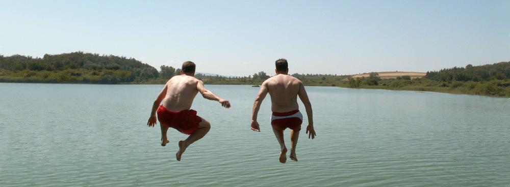 Zwei Männer springen in einen See