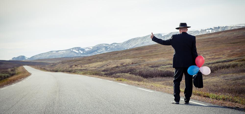 Mann mit Luftballons an einer Straße in einer einsamen Landschaft
