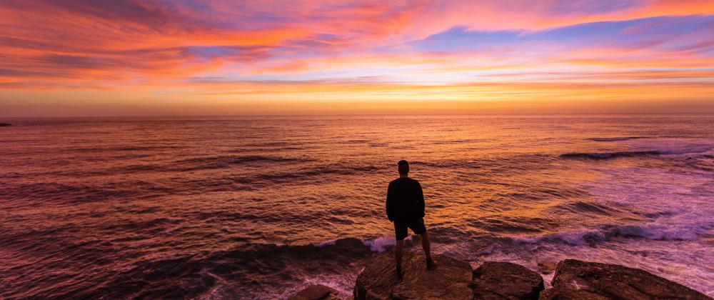 Ein Mann schaut am Abend über das Meer