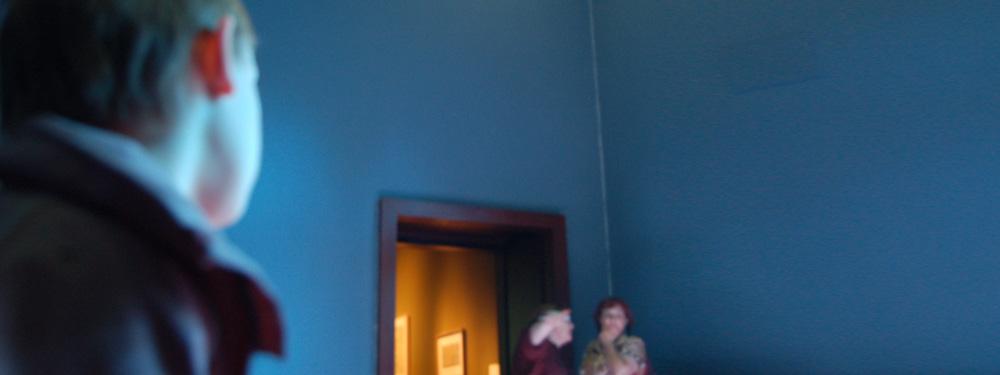 Ein Junge schaut aus einer Zimmerecke auf zwei Erwachsene