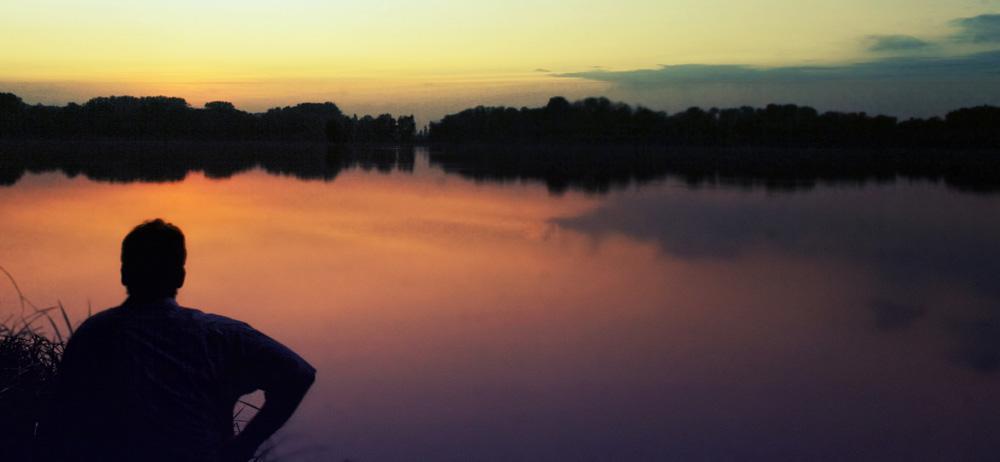ein Mann schaut auf eine Abendstimmung am See