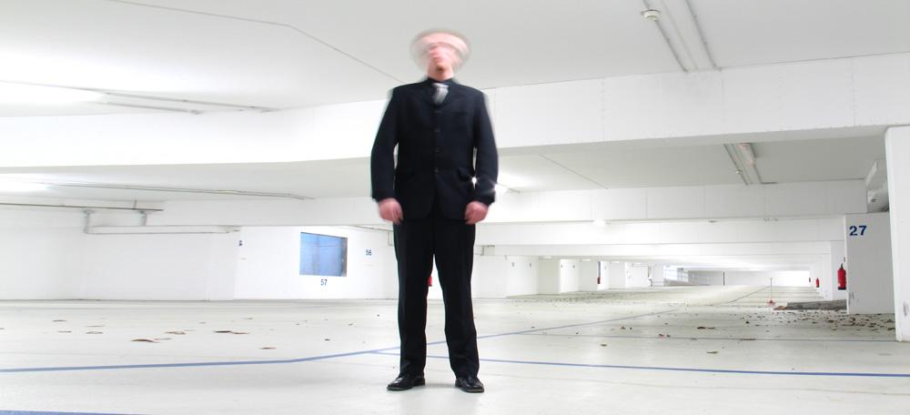 eine Person steht in einer Tiefgarage und schüttelt den Kopf