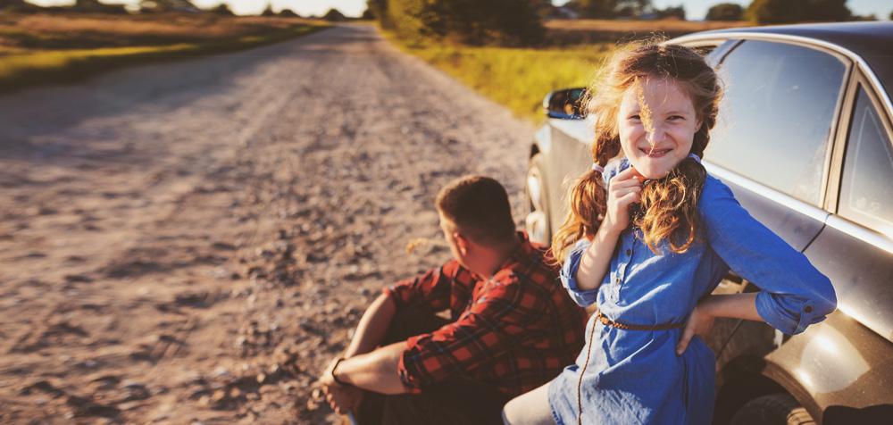 Vater und Tochter mit Auto auf einer Landstraße