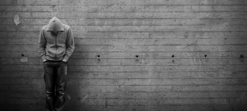 Ein Mann mit Hoodie steht angelehnt an einer Wand und schaut nach unten