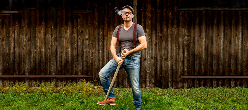 Mann mit Zigarette und Spaten steht vor einem Holztor