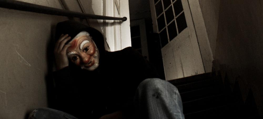 Ein Mann mit einer Maske sitzt auf einer Treppe und stützt seinen Kopf in eine Hand