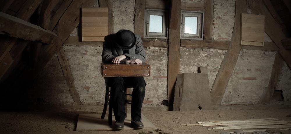 Ein Mann mit einem Koffer sitzt auf einem Dachboden